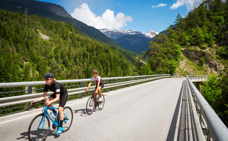 Cyclists on the bridge over the Lienne in St-Léonard / Uvrier, Valais Cycling Tour