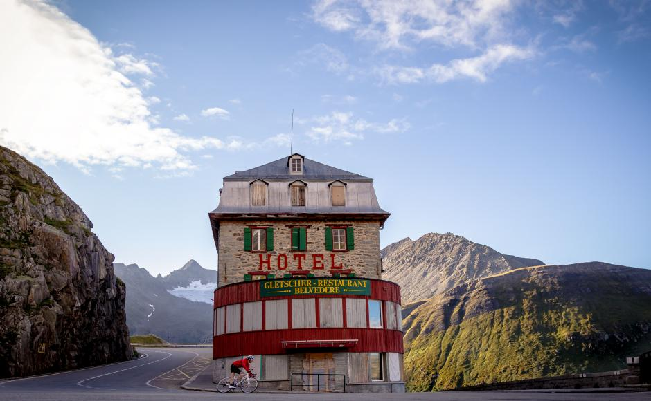 A cyclist on the descent of the Furka passes in front of Hotel Bellevue. Valais Switzerland