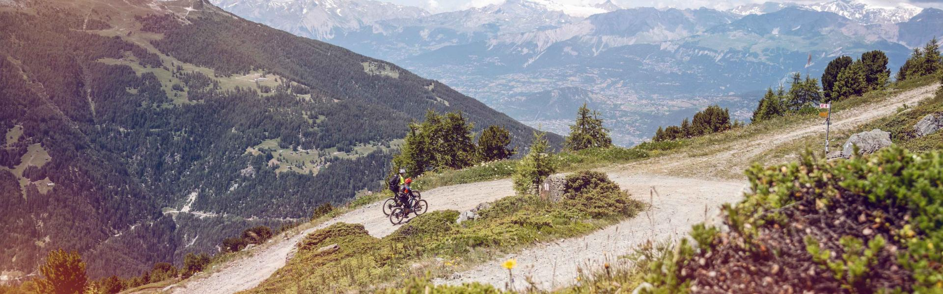 2 people on an e-bike on a climb with a magnificent view, Valais Switzerland
