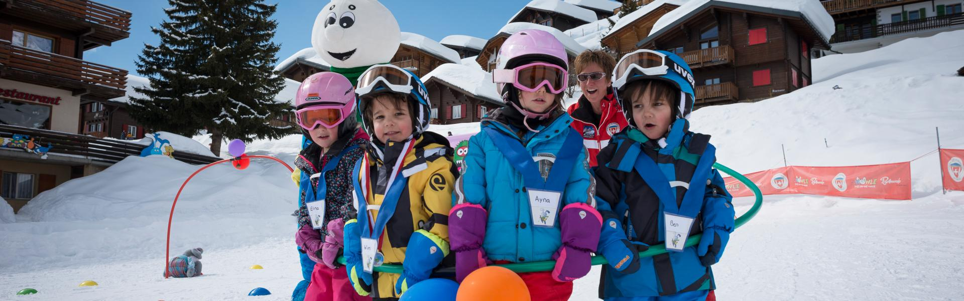 Group photo of the apprentice skiers at the snow garden in Bettmeralp with the mascot