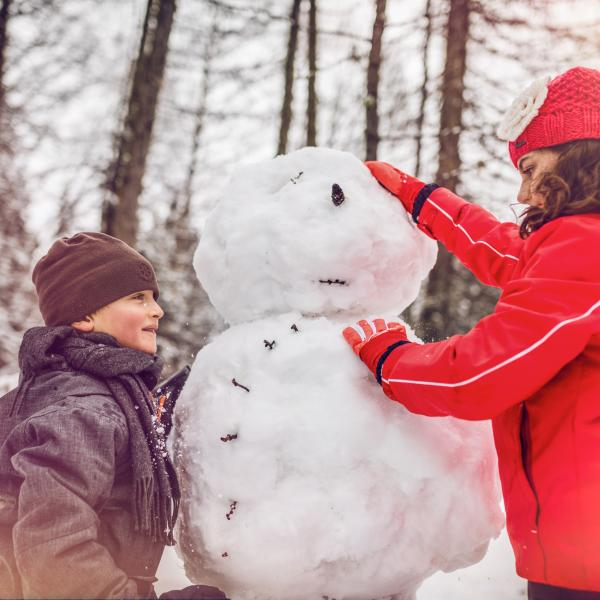 Children building a snowman, winter in Valais, Crans-Montana, family holiday, Switzerland