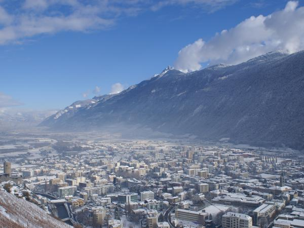 View of the snow-covered town of Martigny from the Forclaz road in winter. Valais. Switzerland