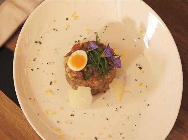 Veal tartare with Entremont honey on a plate with egg, Valais, Switzerland