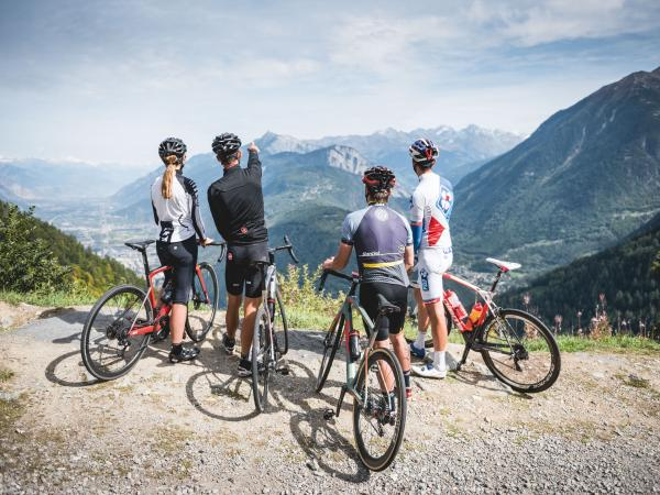 4 cyclists above Martigny-Croix observing the view of the Rhône plain with Catogne. Swiss Valais.