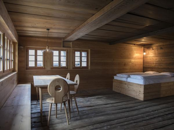 Renovated chalet with bed, chairs and wooden table. Valaisan furniture Valais Wallis Schweiz Switzerland Suisse